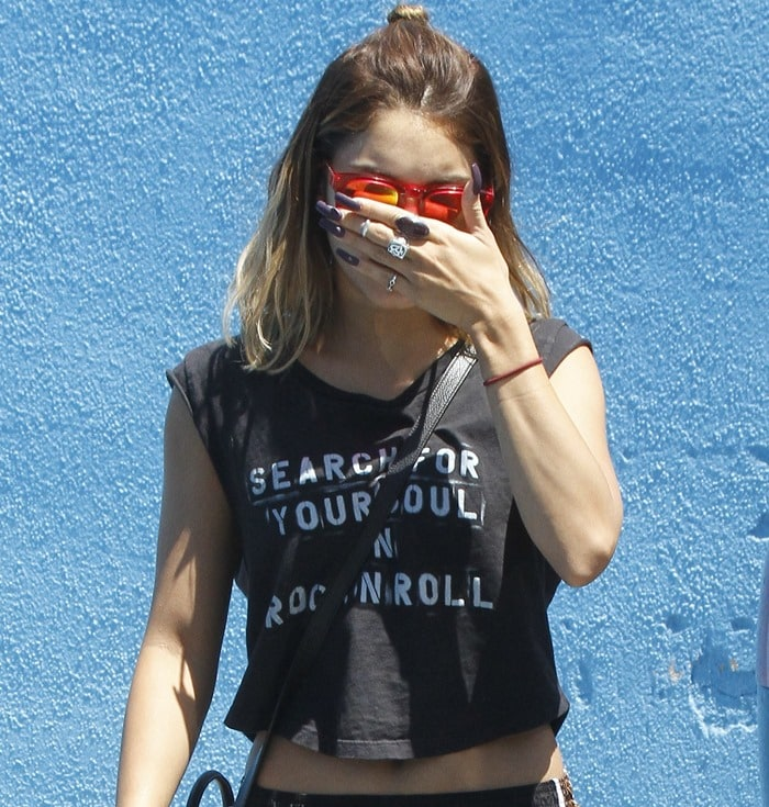 A camera-shy Vanessa Hudgens wearing red Wildfox Classic Fox Deluxe mirror sunglasses