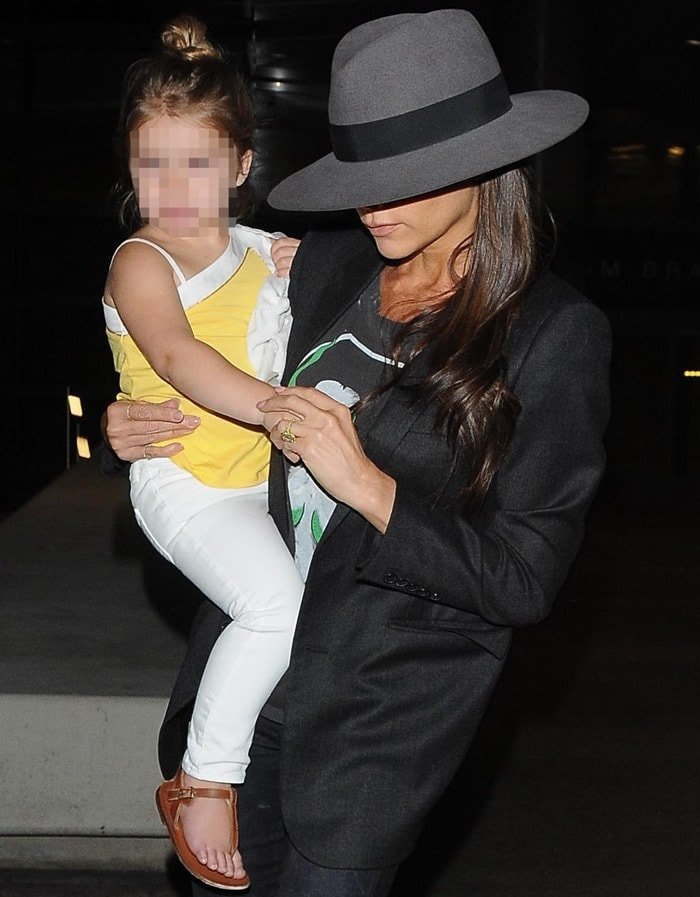 Victoria Beckham carrying daughter Harper at Los Angeles International Airport (LAX) on July 18, 2014