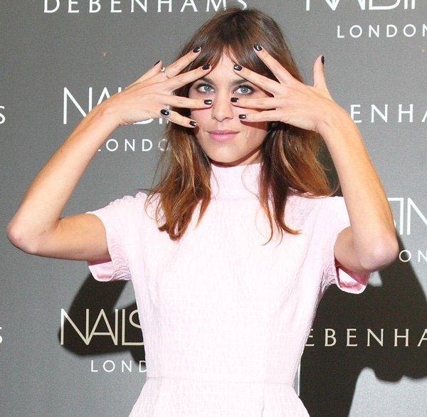 Alexa Chung with smoky eye makeup, tousled hair, and a jet-black mani