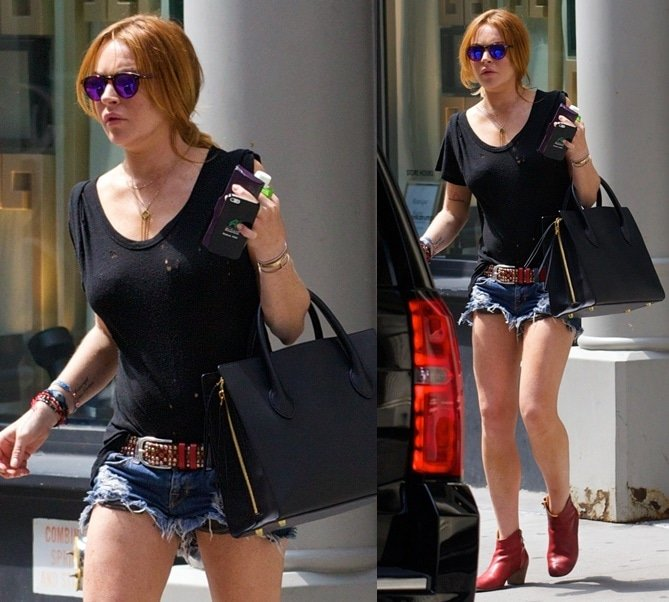 Lindsay Lohan wearing red boots with her short denim cutoffs and a black shirt while flaunting her sexy legs in the SoHo district of New York City on August 21, 2014