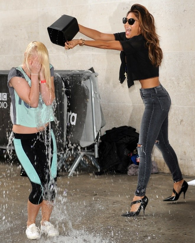 Nicole Scherzinger helping Steffie Croxon, a fan, take the ALS Ice Bucket Challenge by dumping a bucket of ice water on her outside the Radio 1 studios in London, England, on August 25, 2014