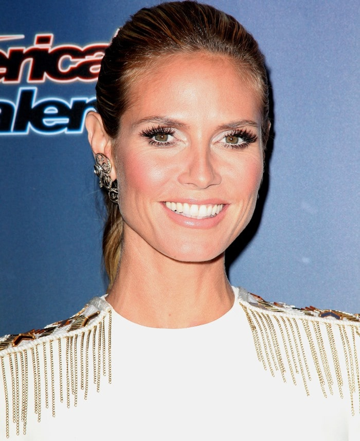 Heidi Klum ina white long-sleeve dress by Versace featuring shoulders with metal chain fringes and beads