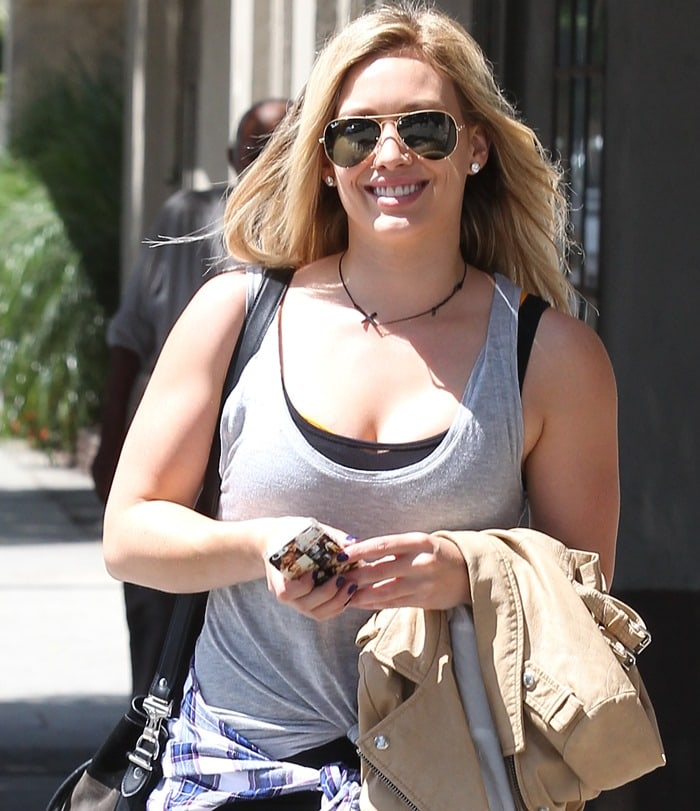 Hilary Duff wearinga loose gray shirt knotted above her hips