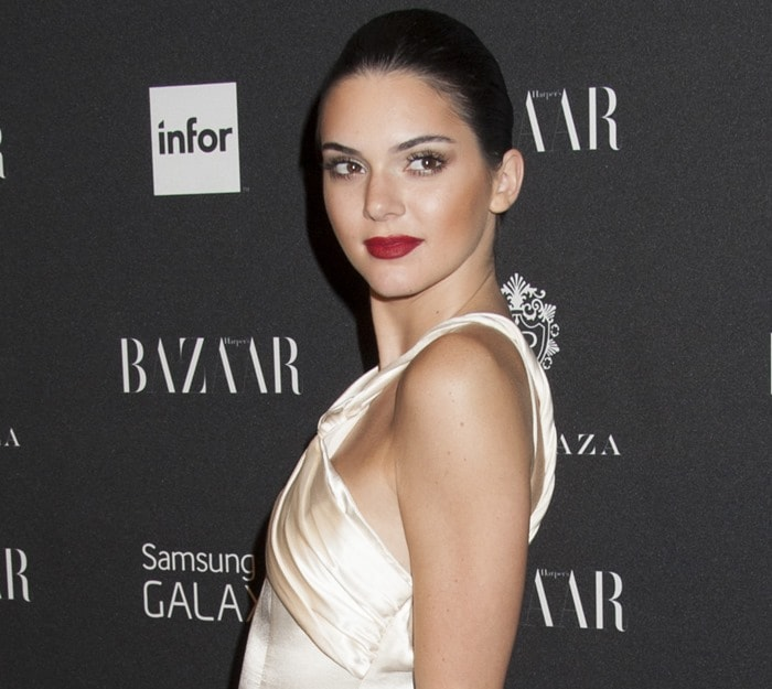 Kendall Jennerin an ivory satin dress by Octavio Carlin featuring a knotted sash and train detailing