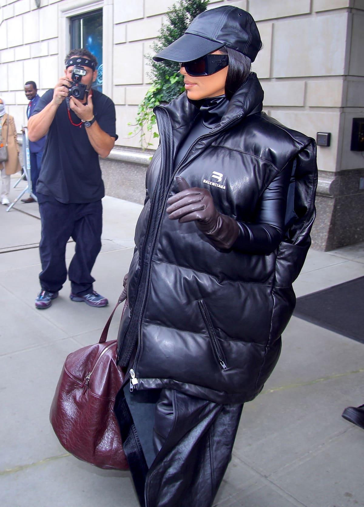 Kim Kardashian wears a puffy black Balenciaga vest with burgundy gloves and a leather baseball cap