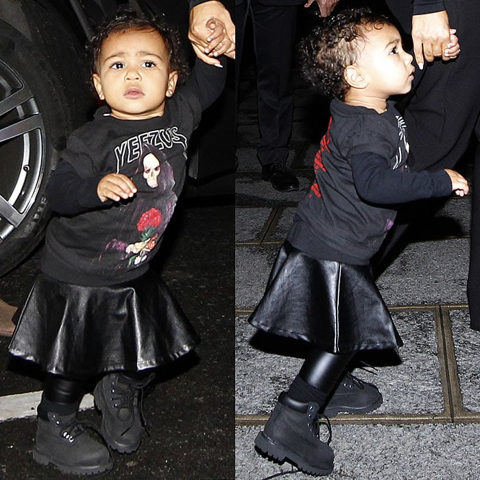 Baby North West in a Yeezus tour sweatshirt, a black leather skirt, black leather leggings, and black Timberland boots