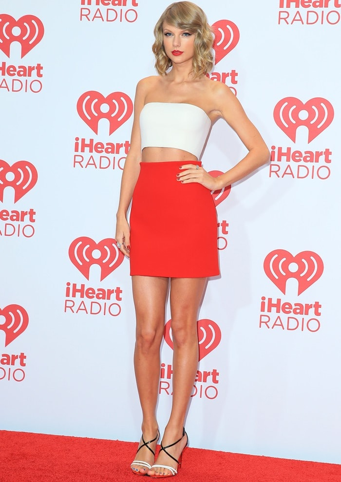 Taylor Swift sported a Calvin Klein Collection white bandeau top paired with a red high-waisted miniskirt