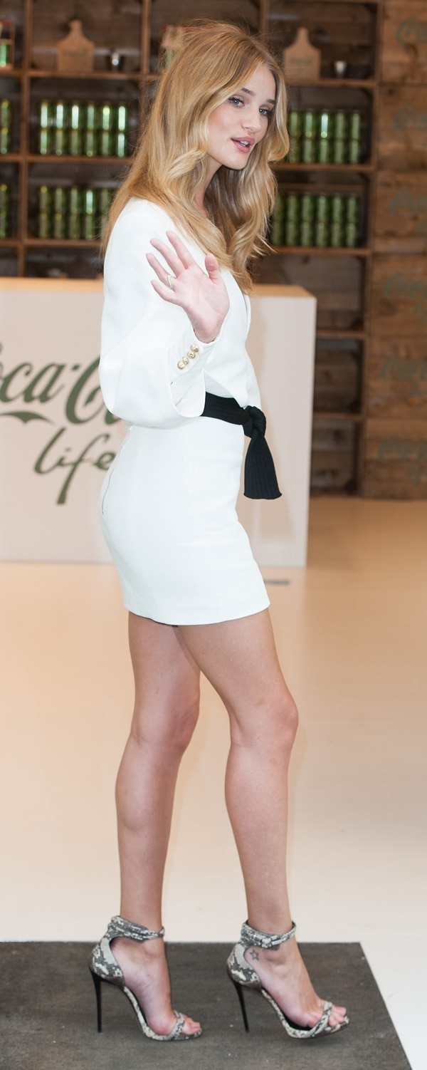 Rosie Huntington-Whiteley in a white Balmain dress with a plunging neckline and snake-printGiuseppe Zanottiankle-wrap sandals