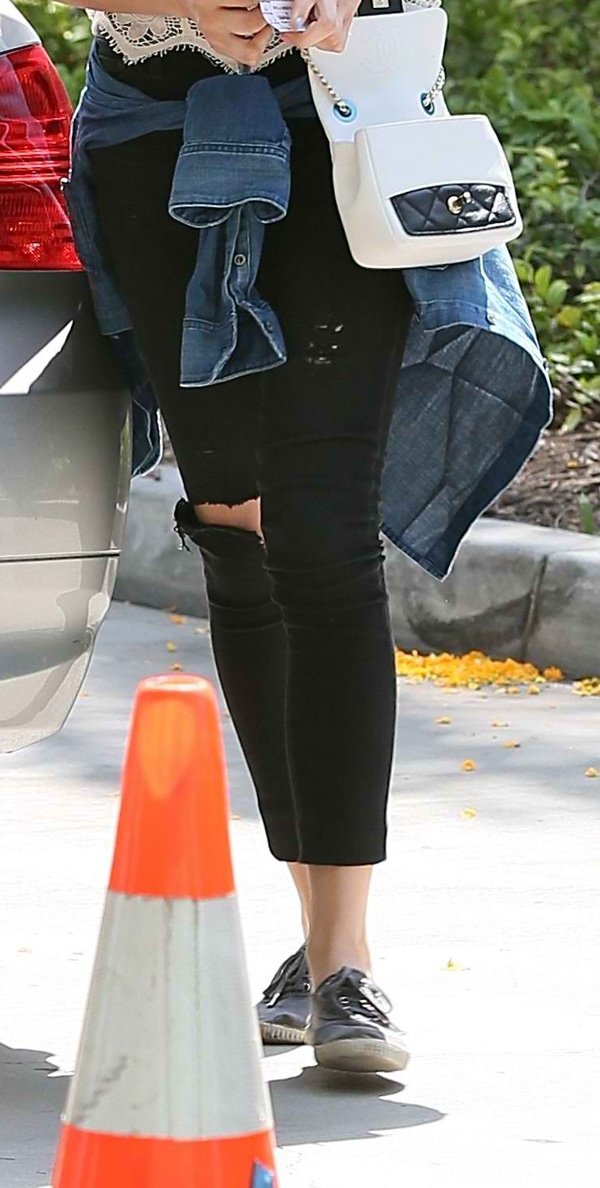 Chloe Moretz wearing black distressed jeans, which also boasts of a cropped hem