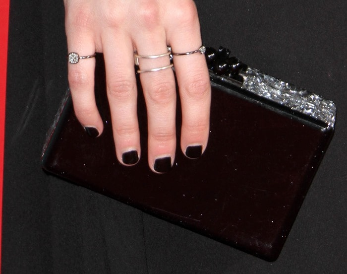 Emma Roberts totes an Edie Parker acrylic clutch and shows off her Meredith Marks rings