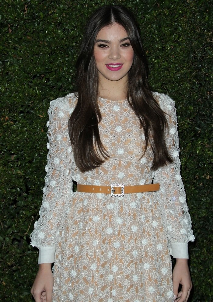 Hailee wearing an embroidered white dress from Michael Kors with long sleeves and round buttons