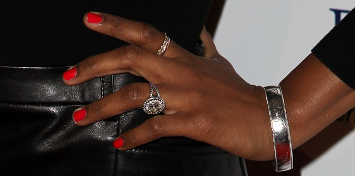 Jennifer Hudson showing off her silver bracelet and glittering rings