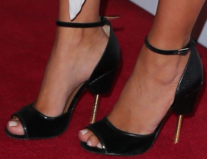 Kim Kardashian shows off her feet inblack lizard-effect leather sandals