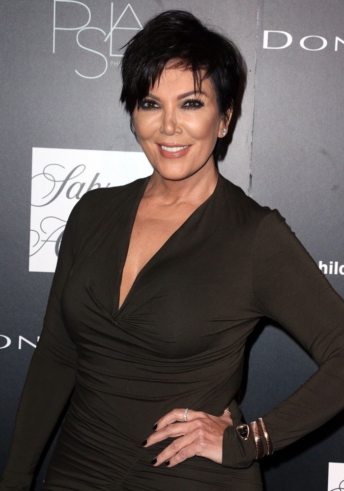 Kris Jenner in a figure-skimming dress detailed with a low-cut neckline