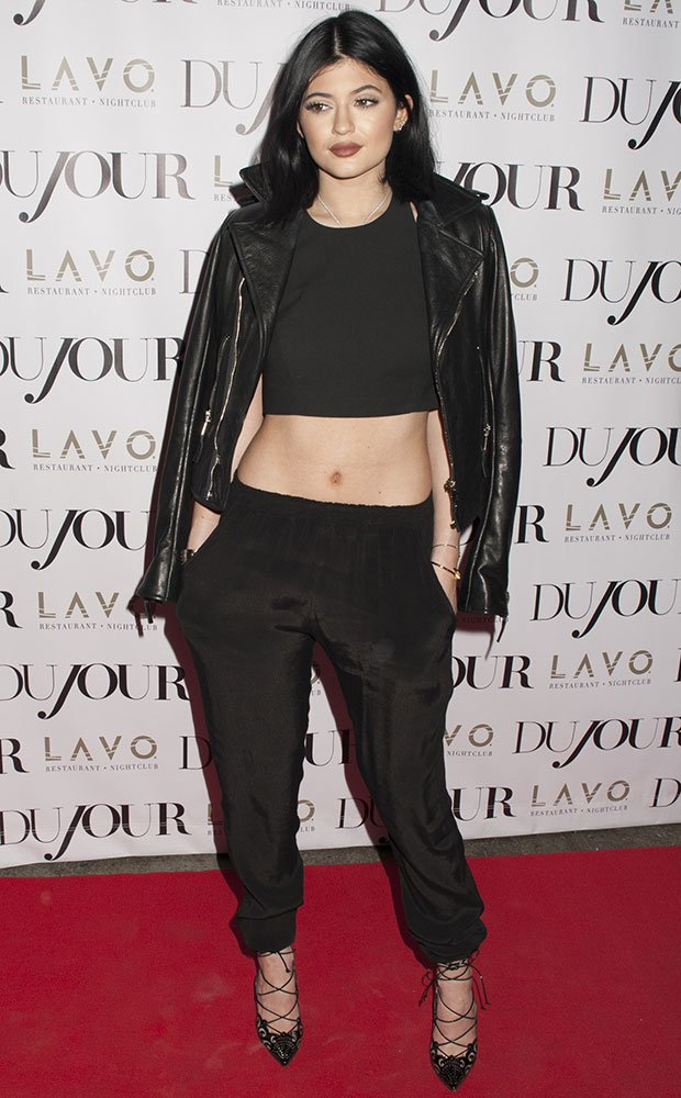 Kylie Jenner wearing a sleeveless crop top and loose pants