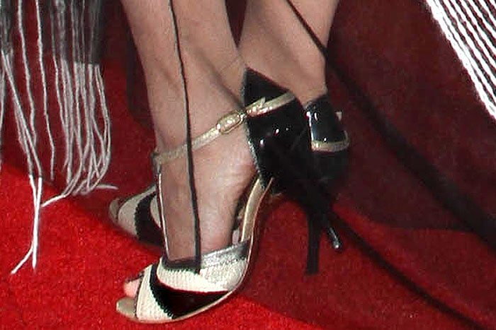 Naomi Grossman's feet in black-and-gold t-strap peep-toe pumps