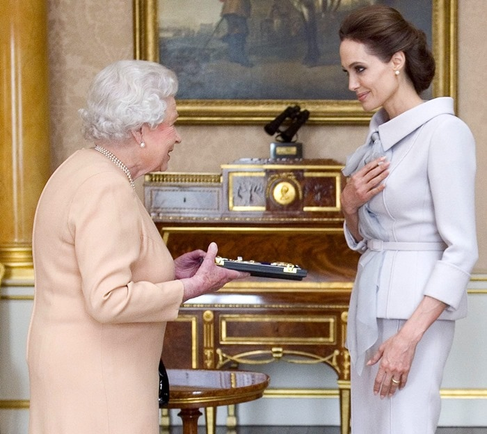 Actress Angelina Jolie presented with the Insignia of an Honorary Dame Grand Cross of the Most Distinguished Order of St Michael and St George by Queen Elizabeth II in the 1844 Room at Buckingham Palace for services to UK foreign policy and the campaign to end war-zone sexual violence. In London, England, on October 10, 2014.