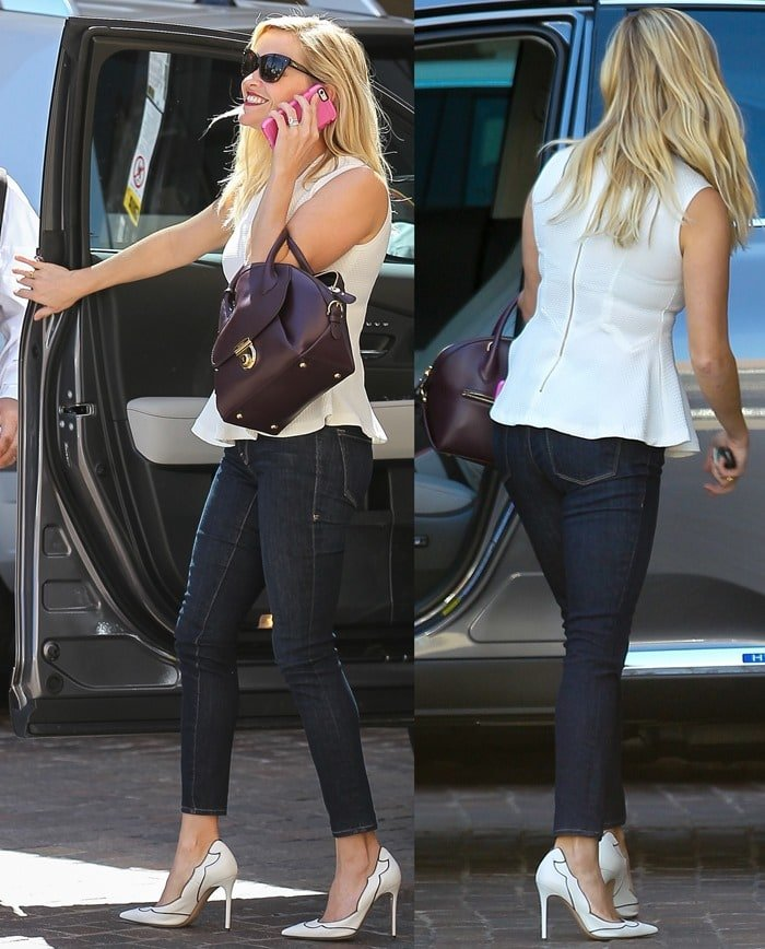 Reese Witherspoon looking well dressed in a peplum top and jeans while talking on her cell phone outside a medical center in Santa Monica on October 2, 2014
