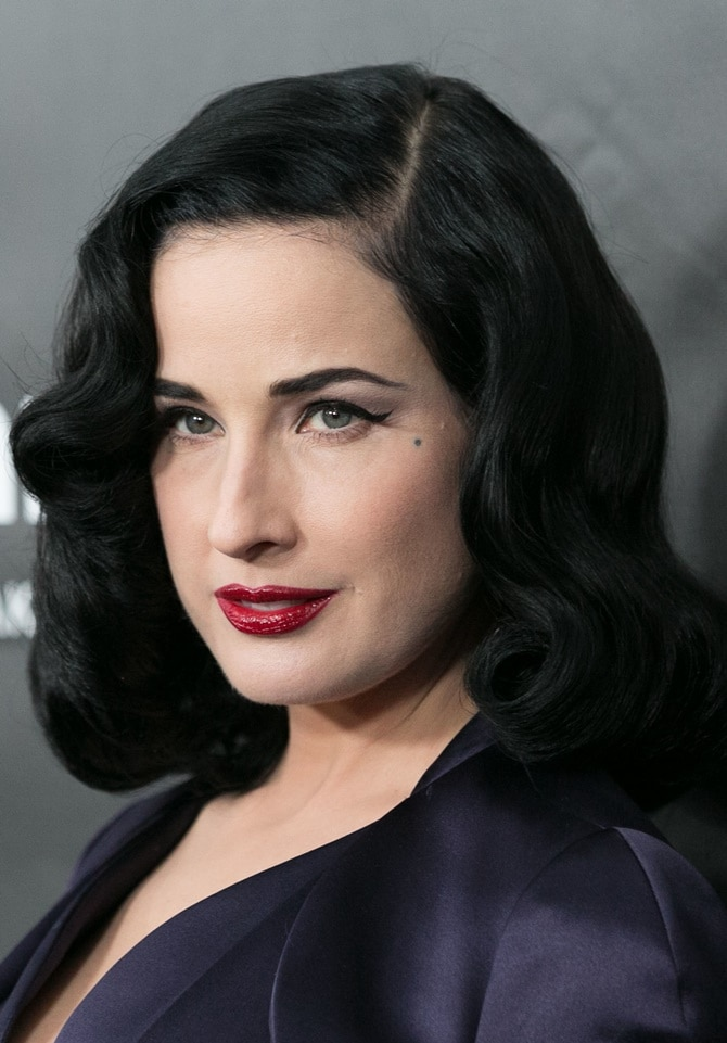 Dita Von Teese wearing her signature beauty look — pale skin, cat eyeliner, and red lipstick