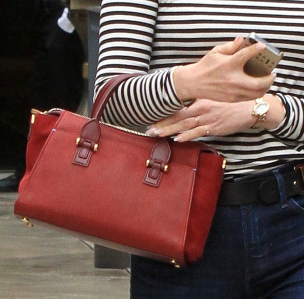 January Jones carries a red mini bag to complement her monochromatic outfit
