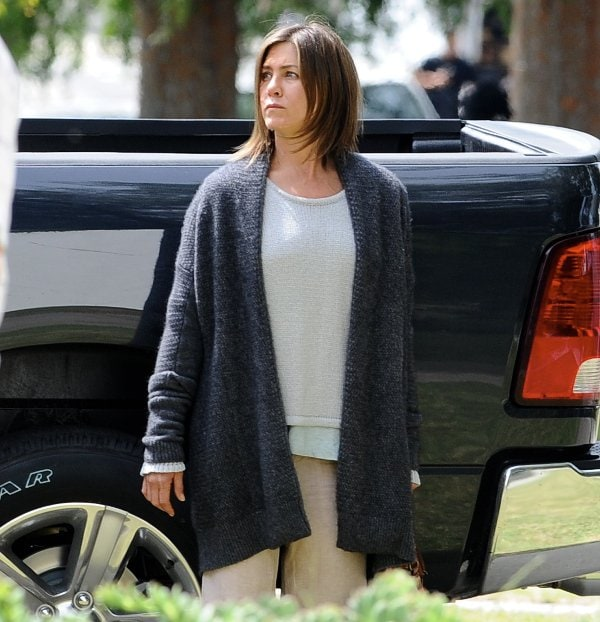 Jen Aniston's grey, white, and khaki outfit match the gloomy theme of the movie