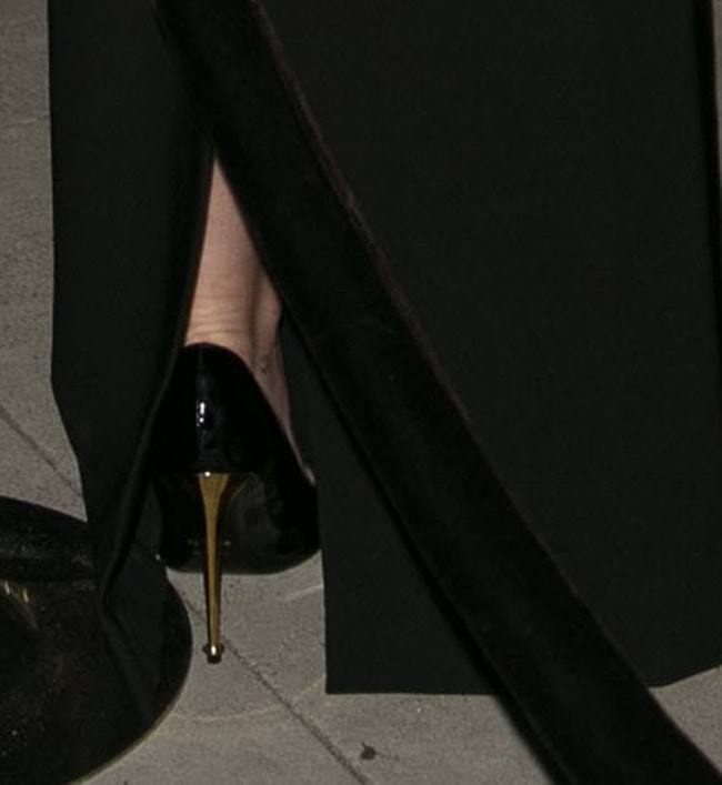 Miley wearing simple black pumps detailed with gold heels