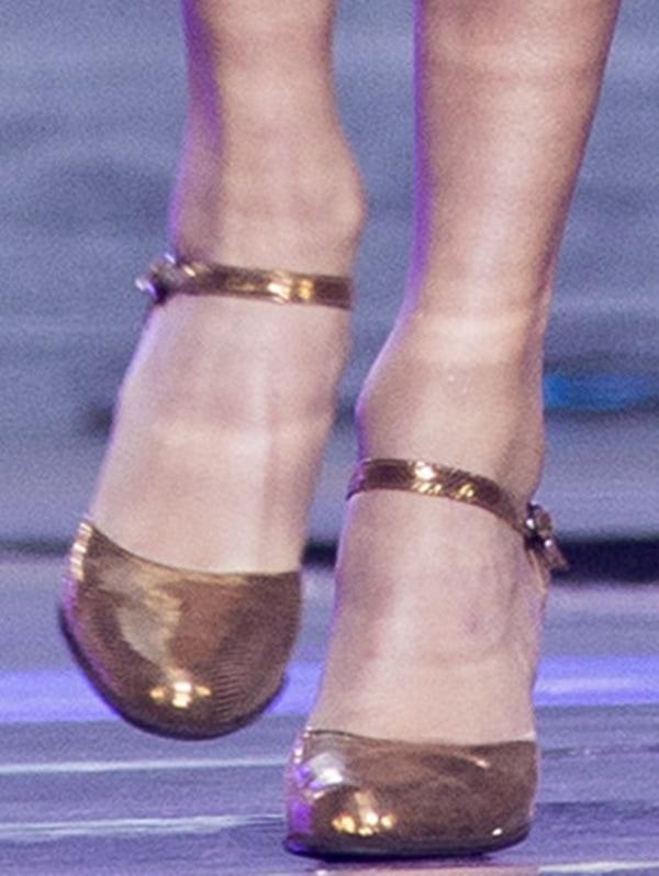 Taylor Swift rocking gold ankle-strap pumps