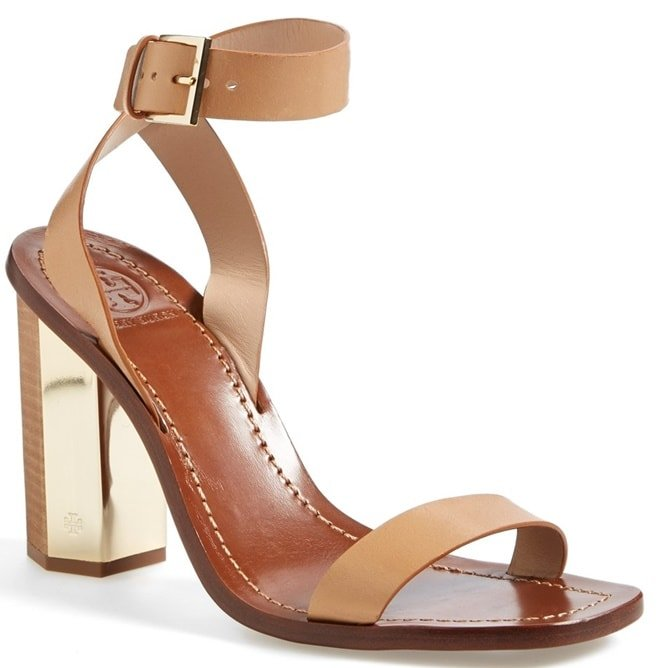 A gilded heel stamped with a subtle Tory Burch logo provides a perfectly polished finish for a clean, minimalist sandal
