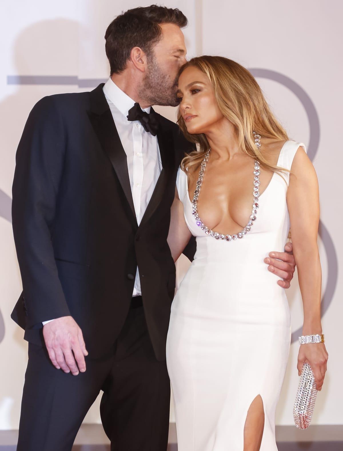 Toting a crystal Judith Leiber clutch, Jennifer Lopez gets a kiss from Ben Affleck