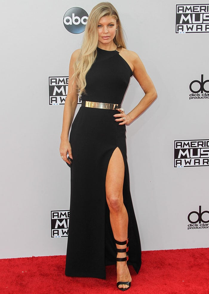 Fergie shows off her sexy legs in a classy black halter-neck gown by Halston Heritage