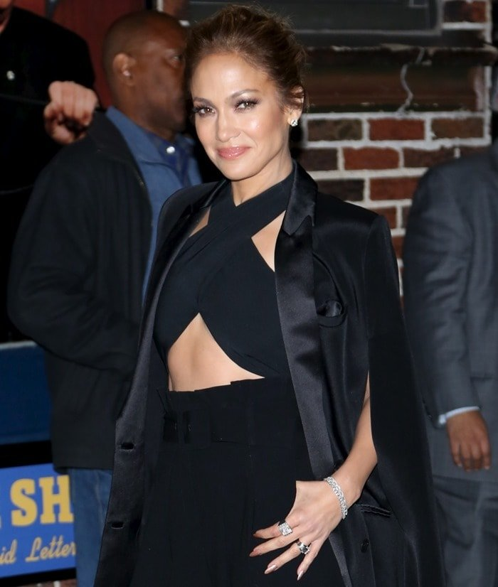 Jennifer Lopez flashing her toned tummy in black-belted wide-leg pants