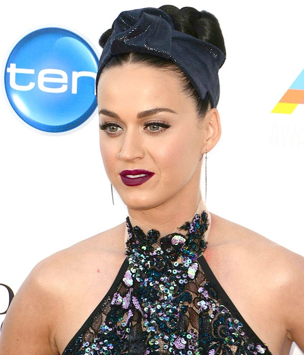 Katy Perry accessorizing with a glittery headwrap, a nose ring, and strand earrings