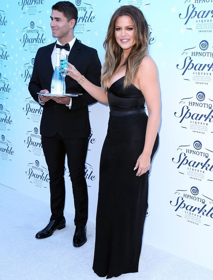 Khloe Kardashian in a black gown featuring a plunging neckline and a curve-hugging silhouette