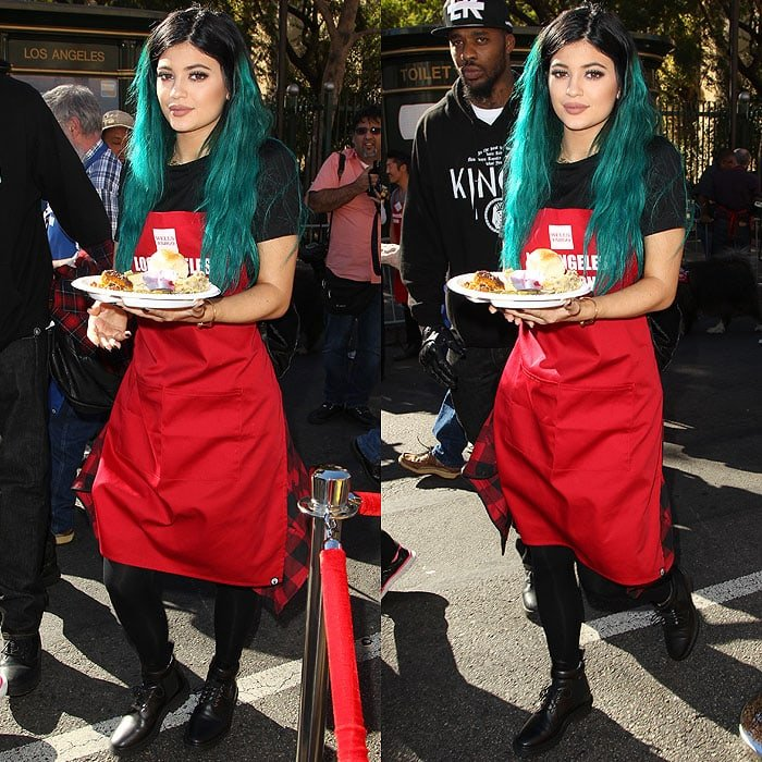 Kylie Jenner holding a Thanksgiving meal plate while wearing Balenciaga biker boots