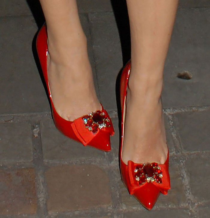 Kylie Minogue'sred patent leather pumps featuresparkling crystal-embellished bows on the pointed toes