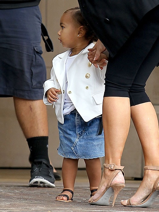 Seventeen-month-old North West sporting her custom Balmain blazer and holding on to mom Kim's hand