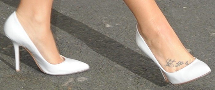 Demi Lovato shows off her feet inwhite patent leather pumps