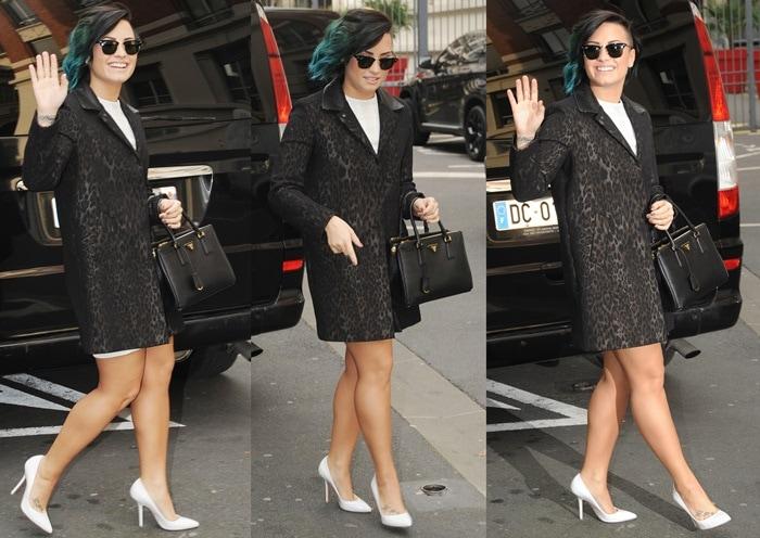 Demi Lovato wearinga Sandro leopard-print jacquard coat over a white dress