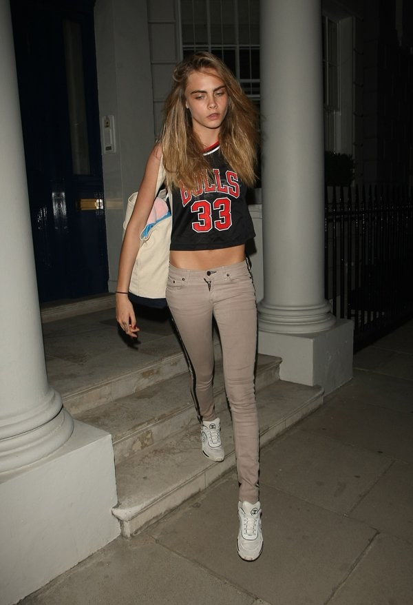 Cara Delevingne leaving her house showing a midriff as she wears a Chicago Bulls 33 shirt in London on July 22, 2013