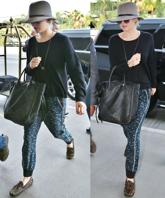 Hunger Games star Jennifer Lawrence wearing a mismatched outfit consisting of a wide-brimmed hat, oversized sunglasses, loose-fitting tapered black trousers with a blue floral design, and leopard-print moccasins