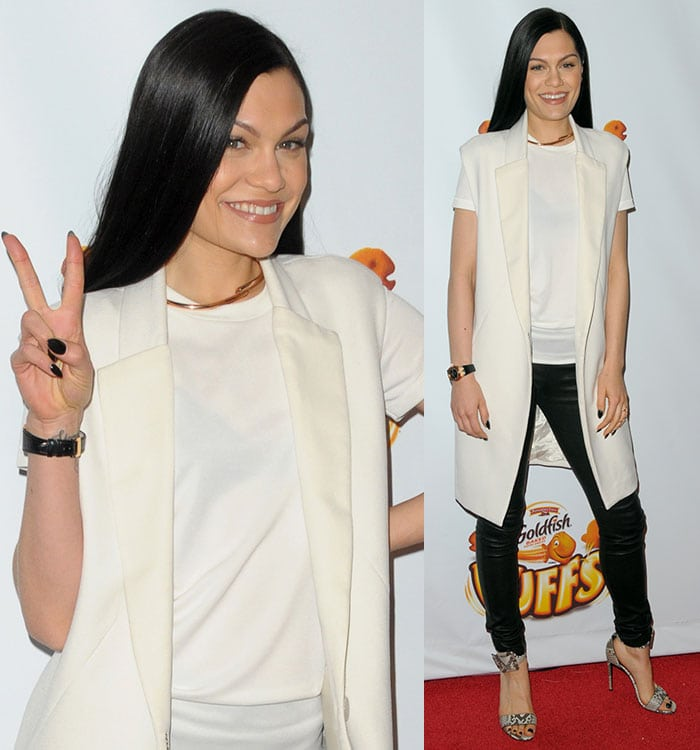 Jessie J covered up in a white top, a pair of black leather pants, and a long cream coat