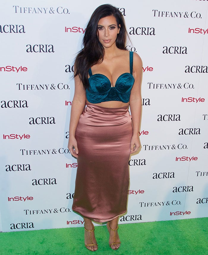 Kim Kardashian paired a green embroidered bralette with a pencil-cut midi skirt in rose satin