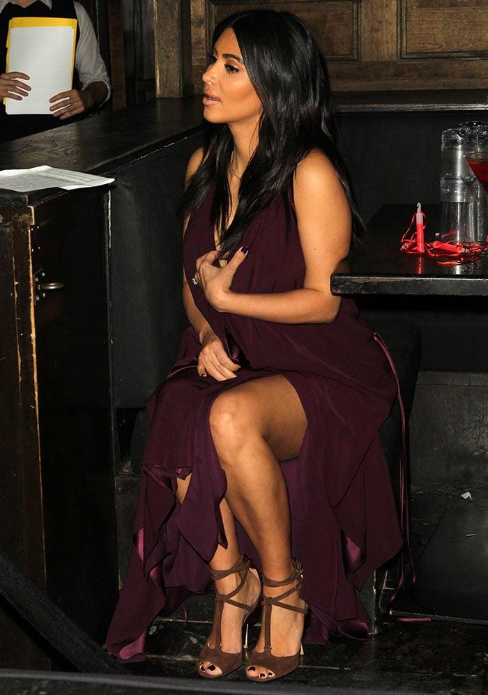 Kim Kardashian shows off her legs in a floor-length burgundy dress