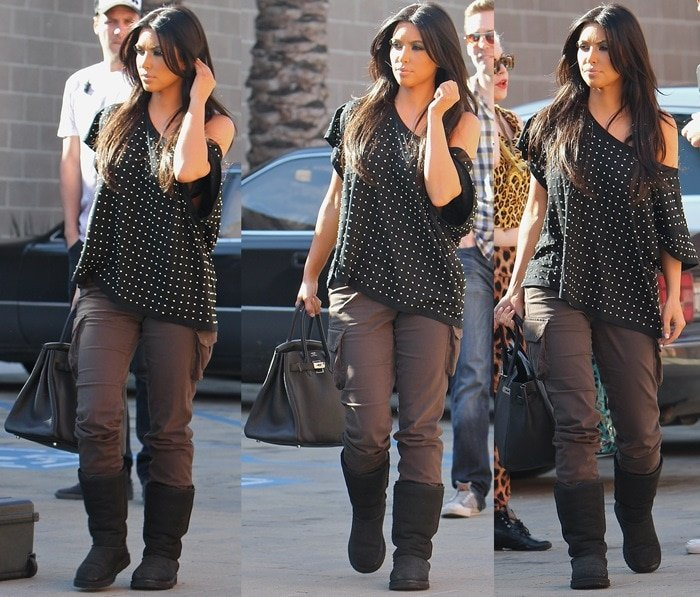 Kim Kardashian styled her black UGG Australia boots with cargo pants by James Jeans, an off-shoulder slouchy black shirt, and a black Hermes Birkin bag