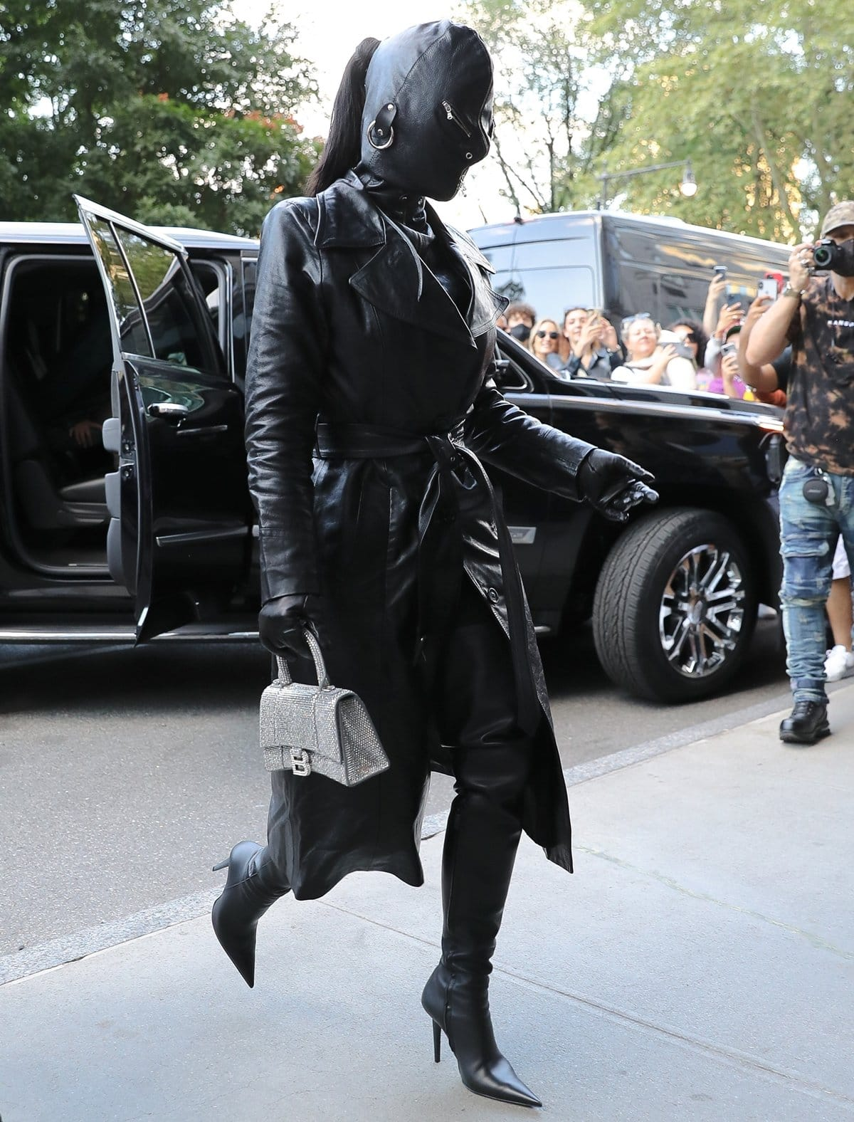 Kim Kardashian wears a black fetish mask with a matching leather trench coat, pants, and stiletto heel boots