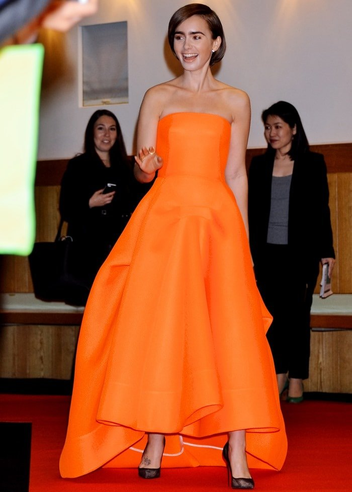 Lily Collins in a fluorescent orange mesh strapless gown from the Maticevski Resort 2015 collection