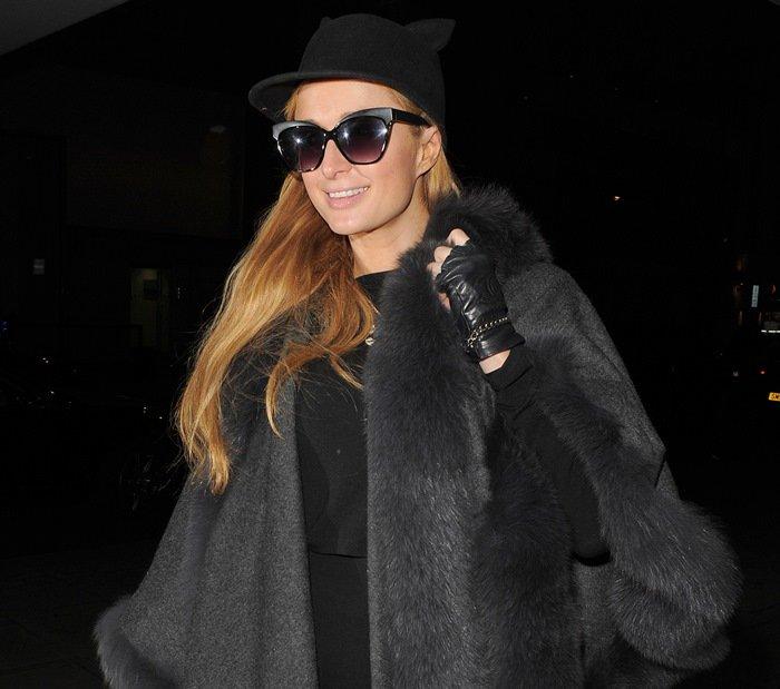 Paris Hilton wears a cashmereU-cape by Sofia Cashmeretrimmed with tonal-dyed fox fur