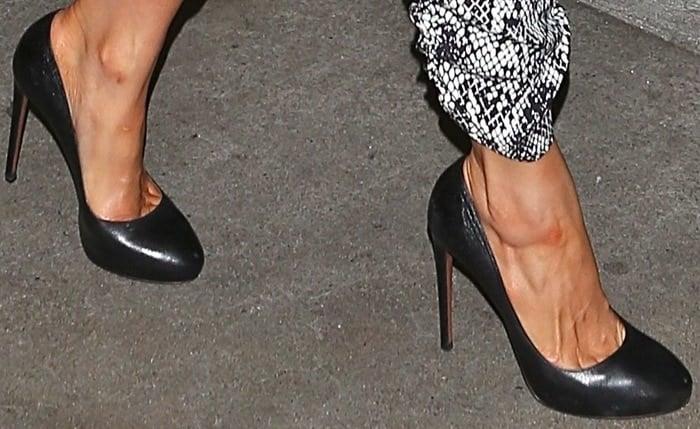 Paris Hilton shows off her feet in black pumps