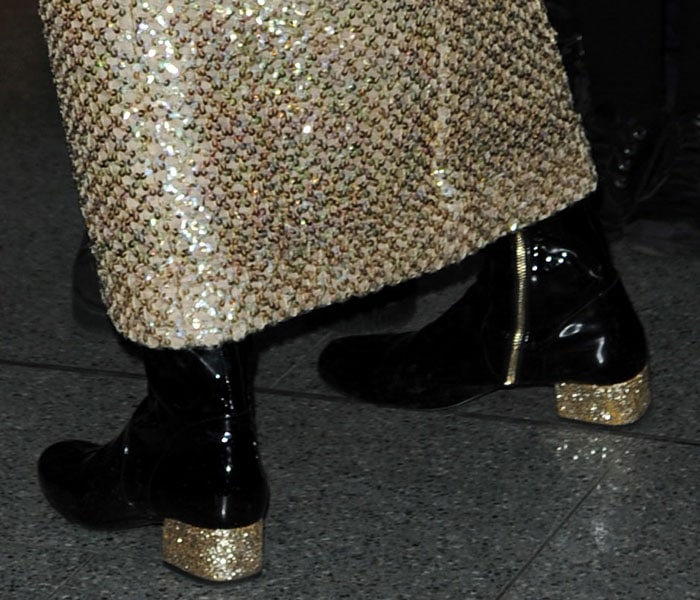 Pixie Lott's black patent boots with partial golden zipper fastenings