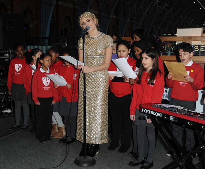 Pixie Lott performing with children from Copenhagen Primary School to raise funds for Penny for London at St. Pancras International in London on December 16, 2014
